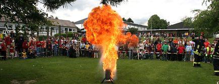 Das Feuer auf dem Schulhof birgt keine Gefahr, es dient der Demonstration einer Brandschutzübung der Feuerwehr.
